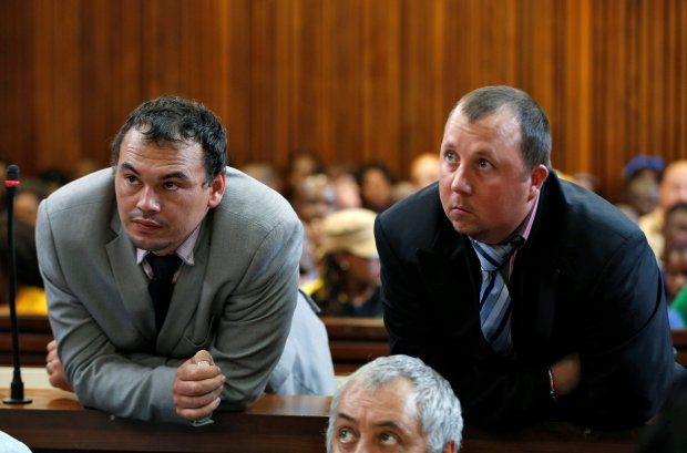 Farmers Willem Oosthuizen and Theo Martins (R) look on during their court appearance as they face sentencing in connection with forcing Victor Mlotshwa into a coffin, threatening to douse him in petrol and burning him alive, at the Middelburg High Court in Mpumalanga province, South Africa, October 23, 2017. REUTERS/Siphiwe Sibeko