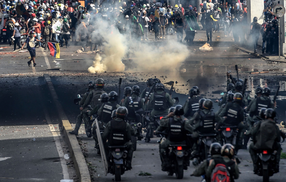 TOPSHOT - Riot police officers confront opposition activists during a demonstration against Venezuelan President Nicolas Maduro in Caracas, on May 26, 2017.  Riot police in Venezuela fired tear gas and water cannon to stop anti-government protesters from marching on a key military installation Friday during the latest violence in nearly two months of unrest. / AFP PHOTO / Juan BARRETO        (Photo credit should read JUAN BARRETO/AFP/Getty Images)