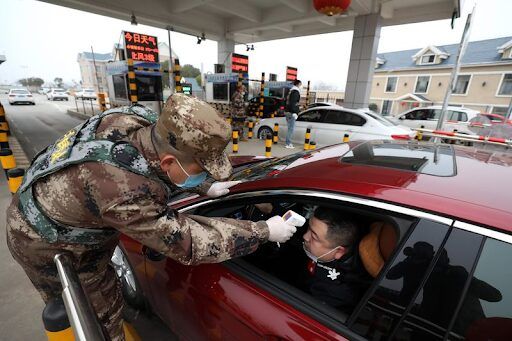 Caption: A militia member checks the body temperature of a driver at a toll gate in Wuhan, Jan. 23.Photographer: Feature China/Barcroft Media via Getty Images from Bloomerg.com