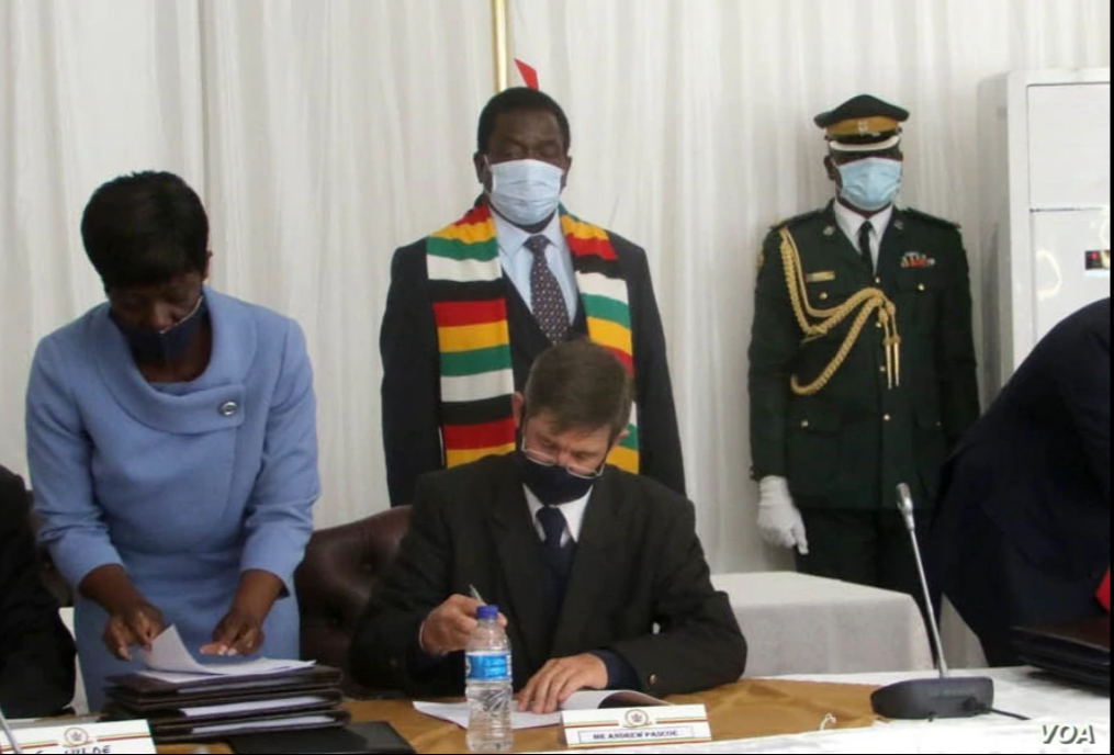 Andrew Pascoe (seated), the president of the Commercial Farmers Union of Zimbabwe, signs the agreement while President Emmerson Mnangagwa (with scarf) waits for his turn, at the State House in Zimbabwe, July 29, 2020. (Columbus Mavhunga/VOA)  Andrew Pascoe (seated), the president of the Commercial Farmers Union of Zimbabwe, signs the agreement while President Emmerson Mnangagwa (with scarf) waits for his turn, at the State House in Zimbabwe, July 29, 2020. (Columbus Mavhunga/VOA)