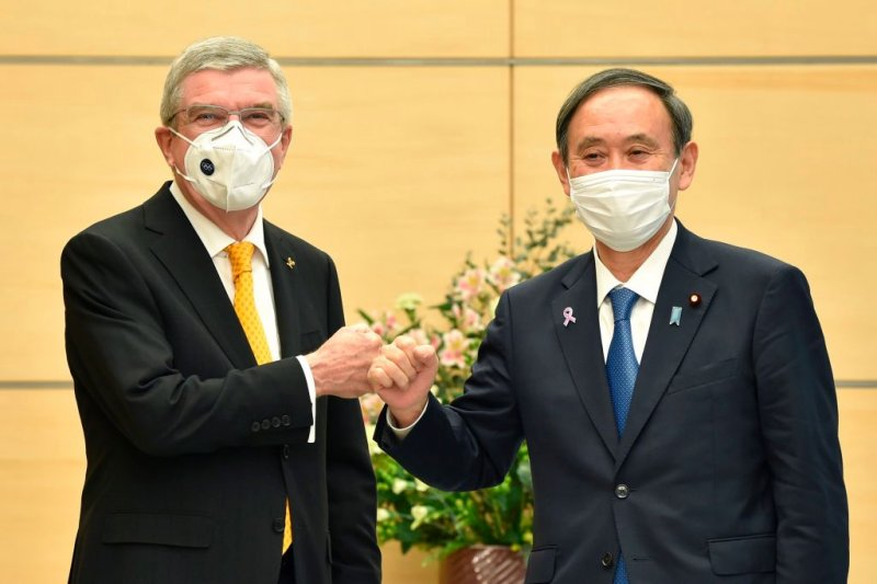Japan's Prime Minister Yoshihide Suga (R) greets International Olympic Committee (IOC) president Thomas Bach (L) during their meeting in Tokyo on November 16, 2020. (Photo by Kazuhiro NOGI / POOL / AFP) (Photo by KAZUHIRO NOGI/POOL/AFP via Getty Images)